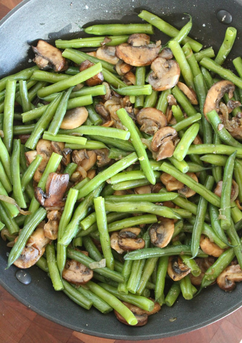 cooking Green Beans with Mushrooms and Shallots in a skillet