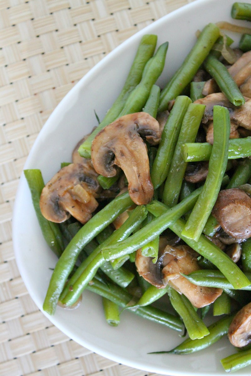 Green Beans with Mushrooms and Shallots on a white platter set on a white woven placemat