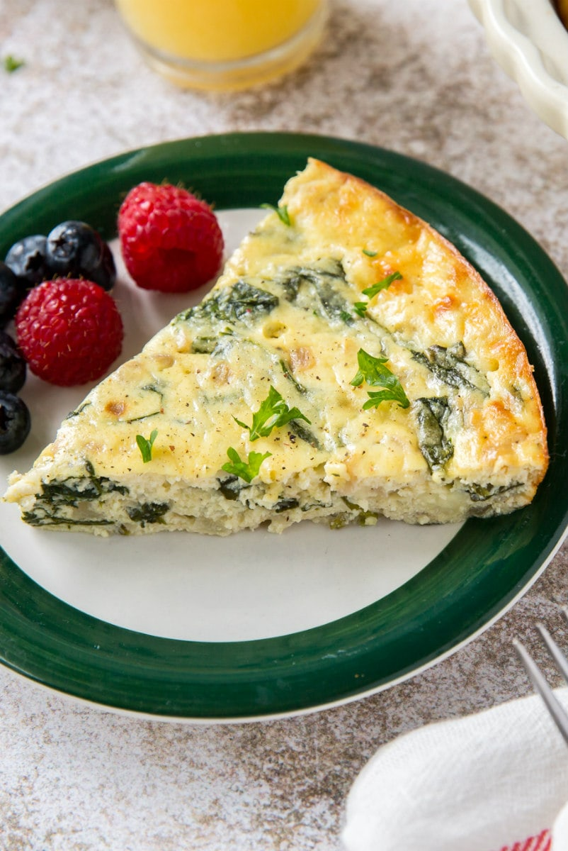 slice of spinach and cheese quiche on a plate