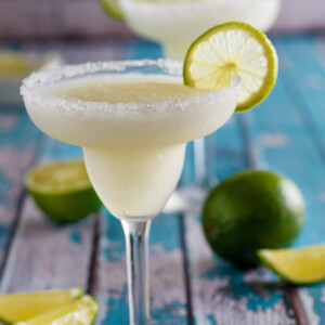 mock margaritas in margarita glasses. fresh lime garnish and wedges on display too