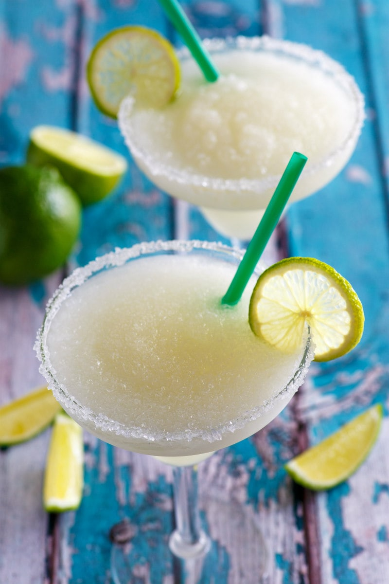 two mock margaritas with lime garnish set on a rustic turquoise board
