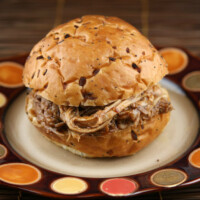 root beer pulled pork sandwich sitting on a brown and white plate with orange and yellow polka dots