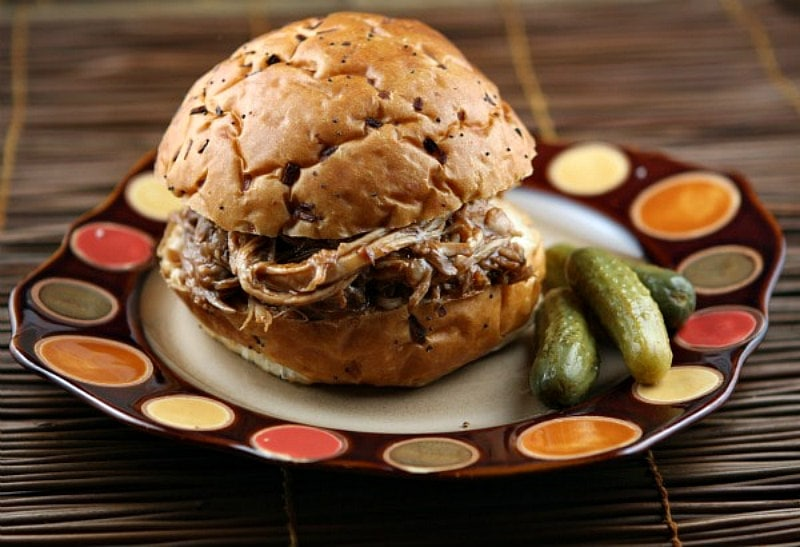 root beer pulled pork sandwich sitting on a brown and white plate with two pickles on the side on an orange and yellow polka dots