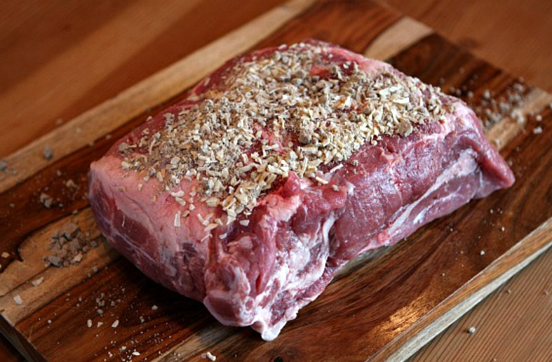 pork roast on a cutting board, topped with spices