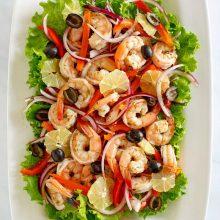 overhead shot of spicy lemon shrimp salad surrounded by green lettuce leaves on a white platter