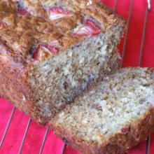 loaf of strawberry oatmeal banana bread sliced open and sitting on a cooling rack on a red cloth napkin