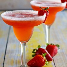 two strawberry margaritas in margarita glasses garnished with strawberries