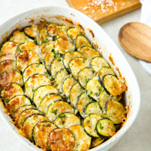 zucchini and tomato gratin in a white casserole dish with a wooden cutting board with cheese on it and a wooden spoon on the side