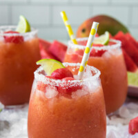 watermelon mango margaritas with yellow straws and lime garnishes