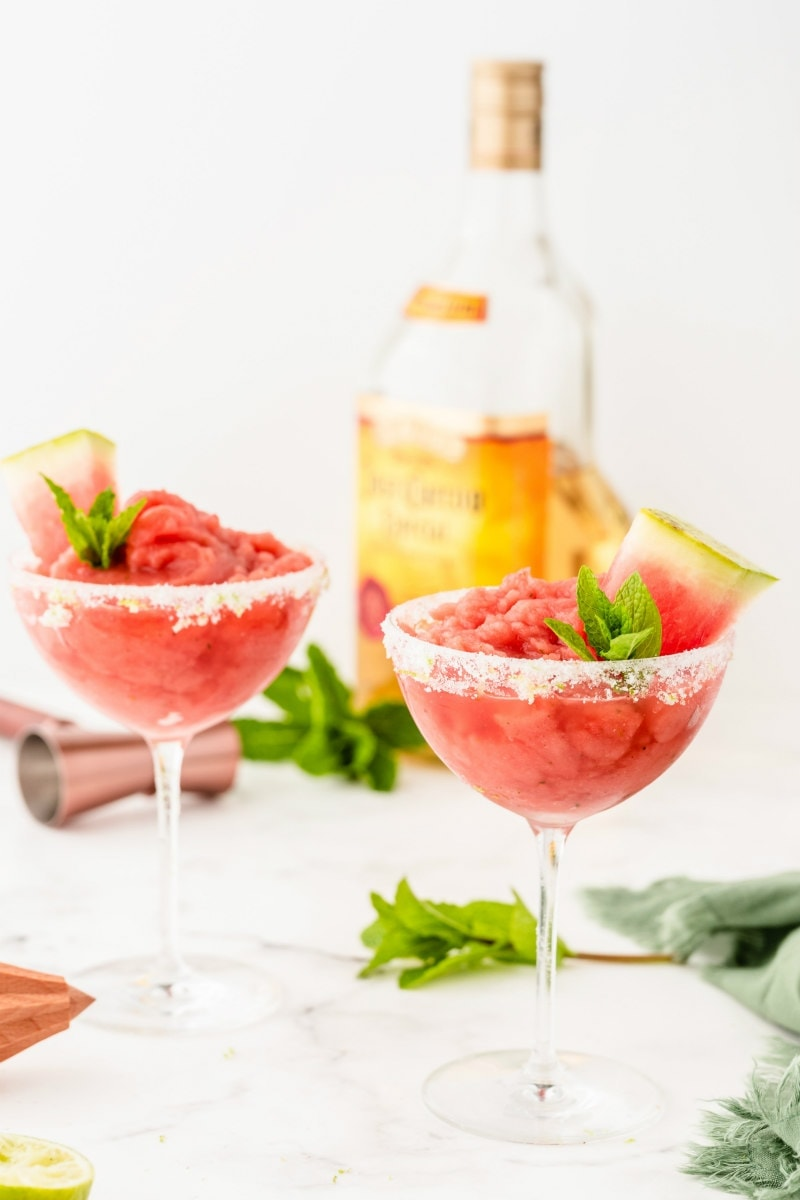 two watermelon mint margaritas garnished with mint and watermelon with a bottle of tequila in the background