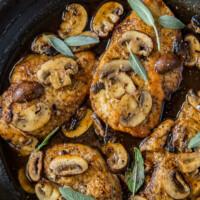 chicken marsala garnished with fresh sage in a skillet