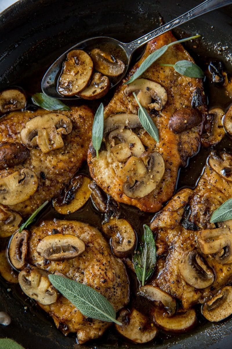 Chicken marsala in a skillet garnished with fresh sage