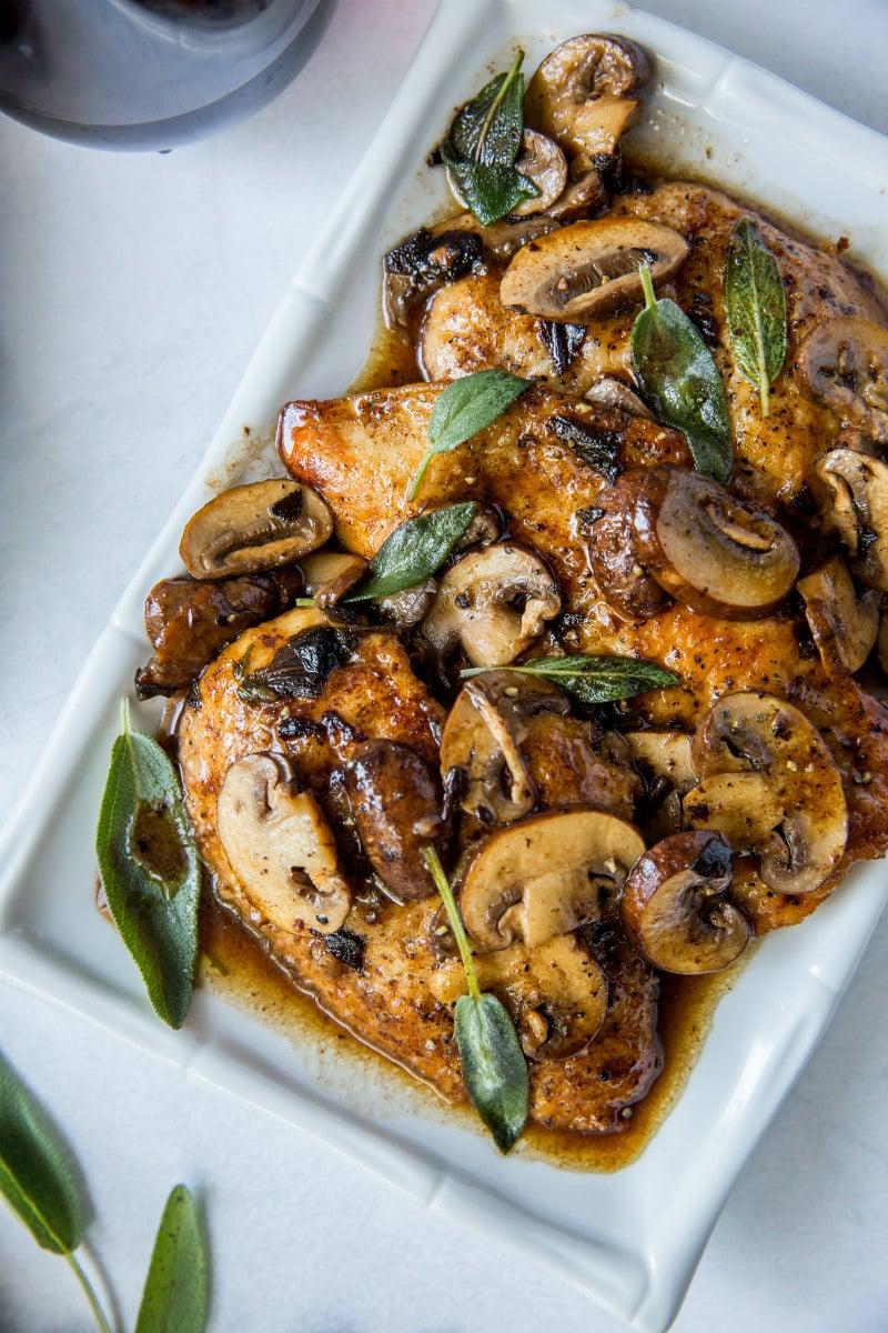 chicken marsala garnished with fresh sage on a white platter