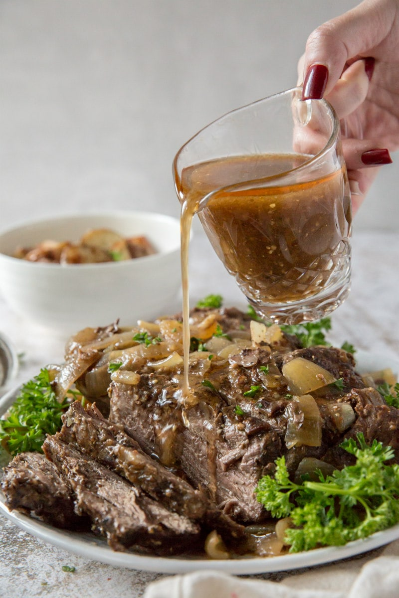 Pouring gravy on Black Forest Pot Roast