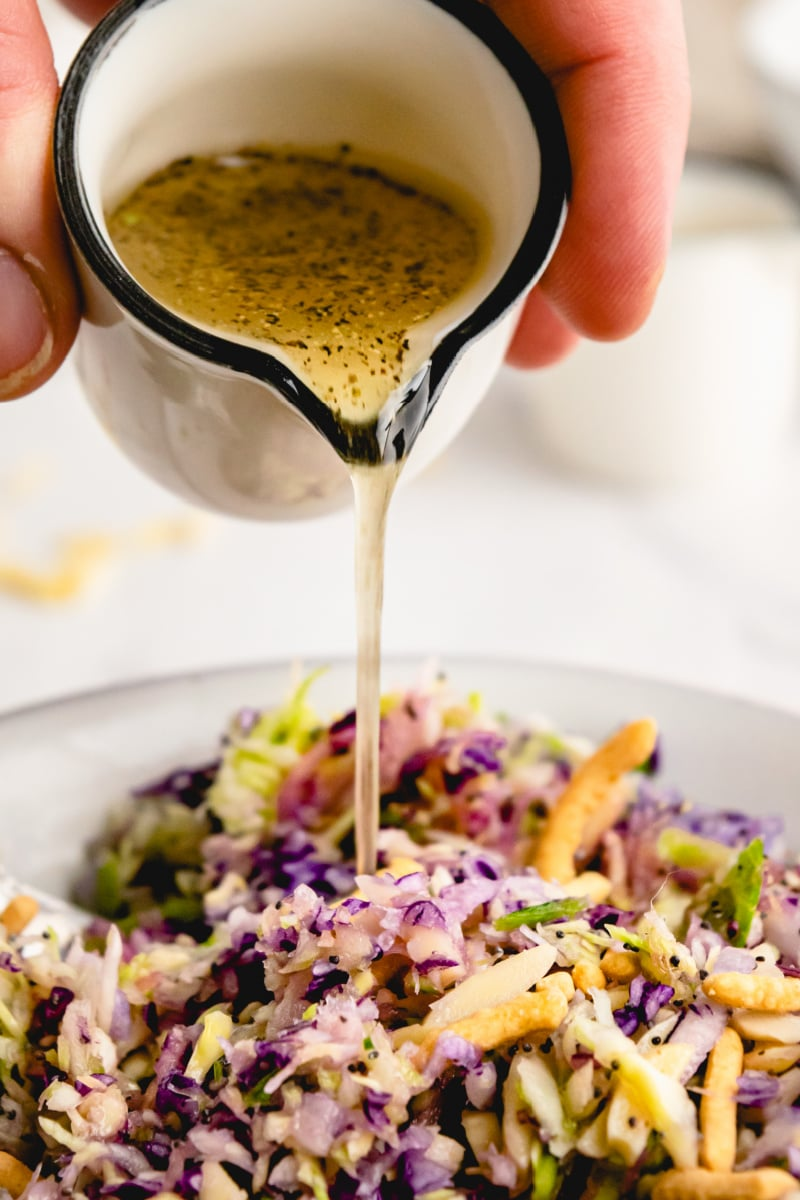 dressing being poured onto salad