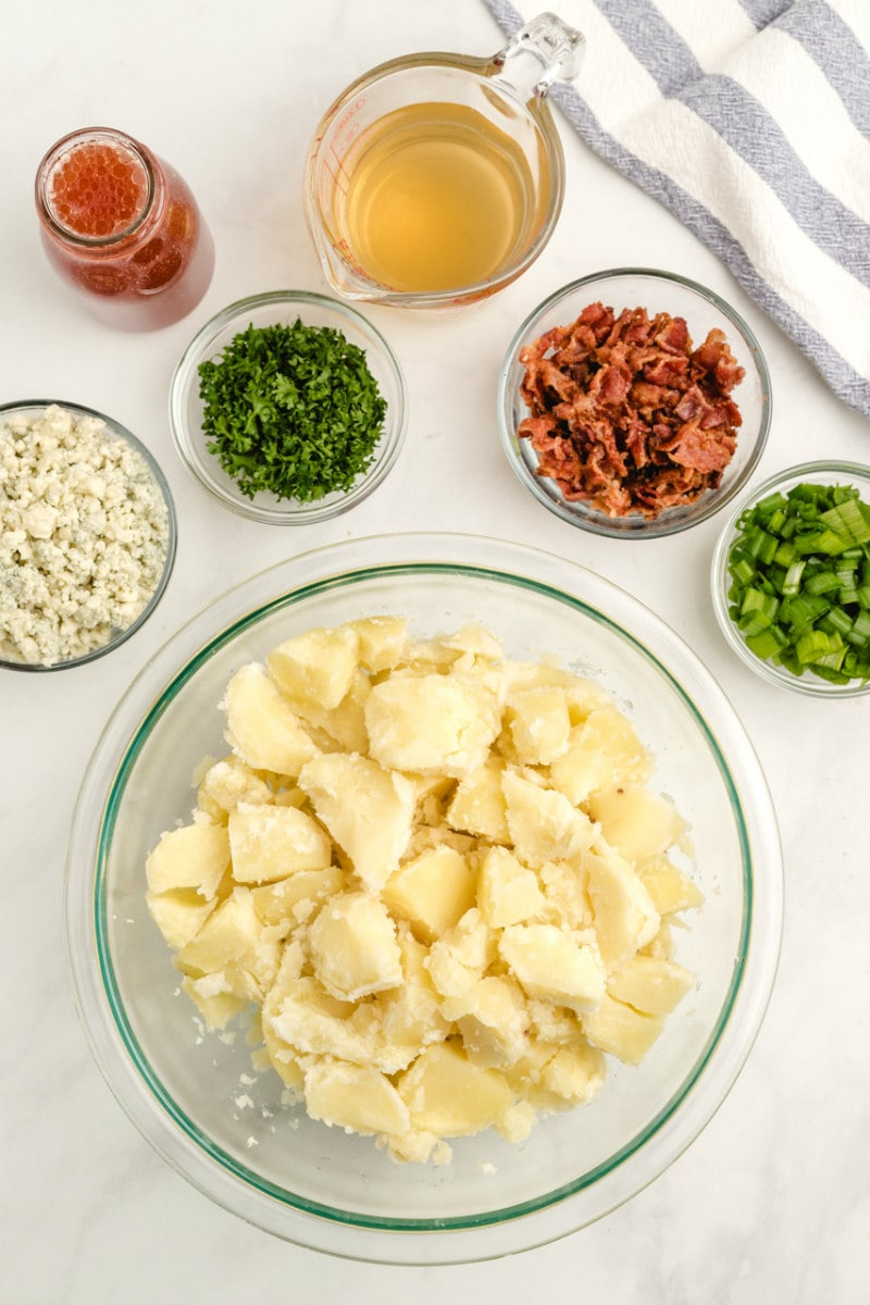 overhead display of ingredients needed for blue cheese and bacon potato salad in glass bowls