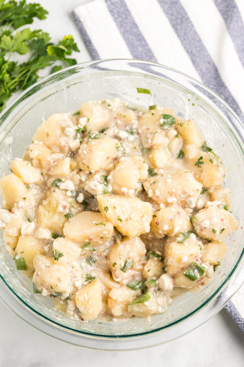 blue cheese potato salad in a glass bowl displayed on a white and blue striped napkin with parsley garnish