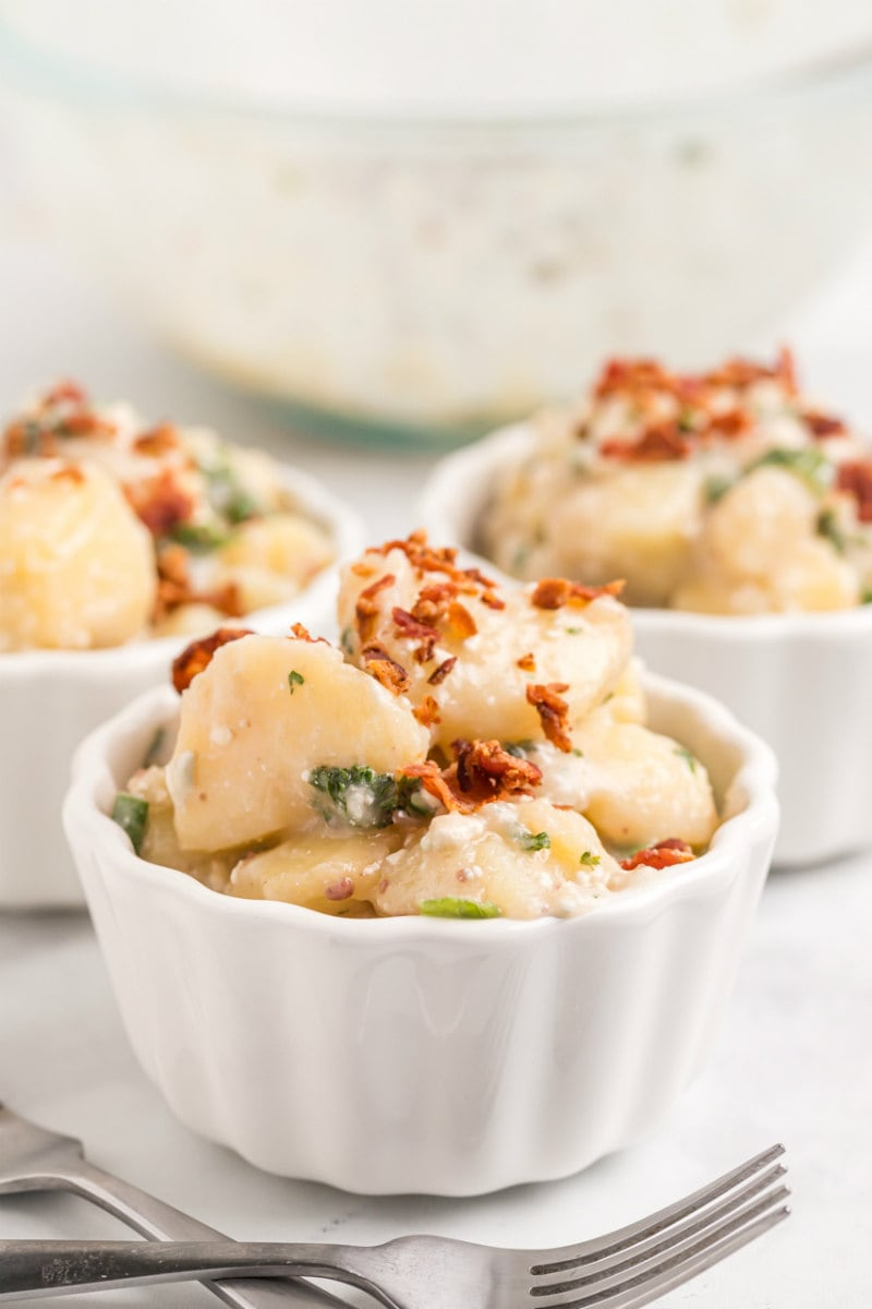 single servings of blue cheese and bacon potato salad in white bowls