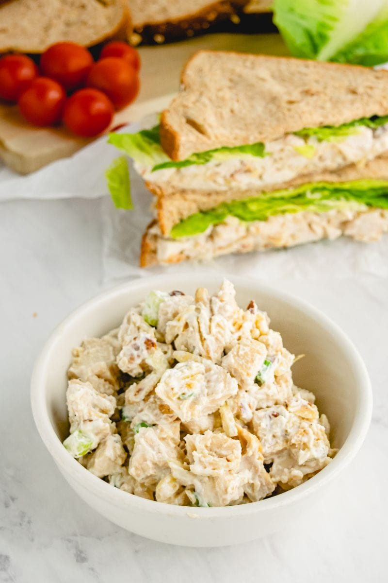 chicken almond salad in bowl with sandwich in background