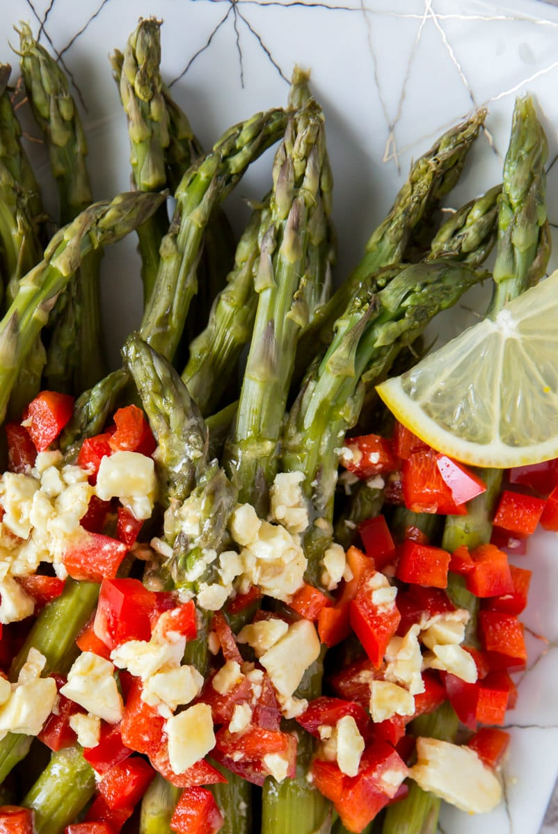 close up of chilled asparagus with feta vinaigrette and chopped red bell peppers and lemon slice