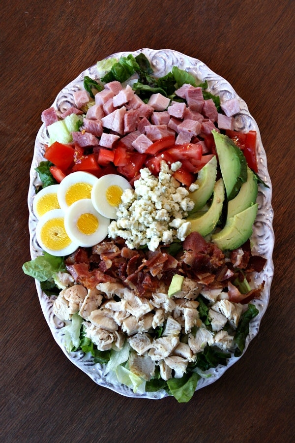 overhead shot of cobb salad on an oval white plate set on a wood table background