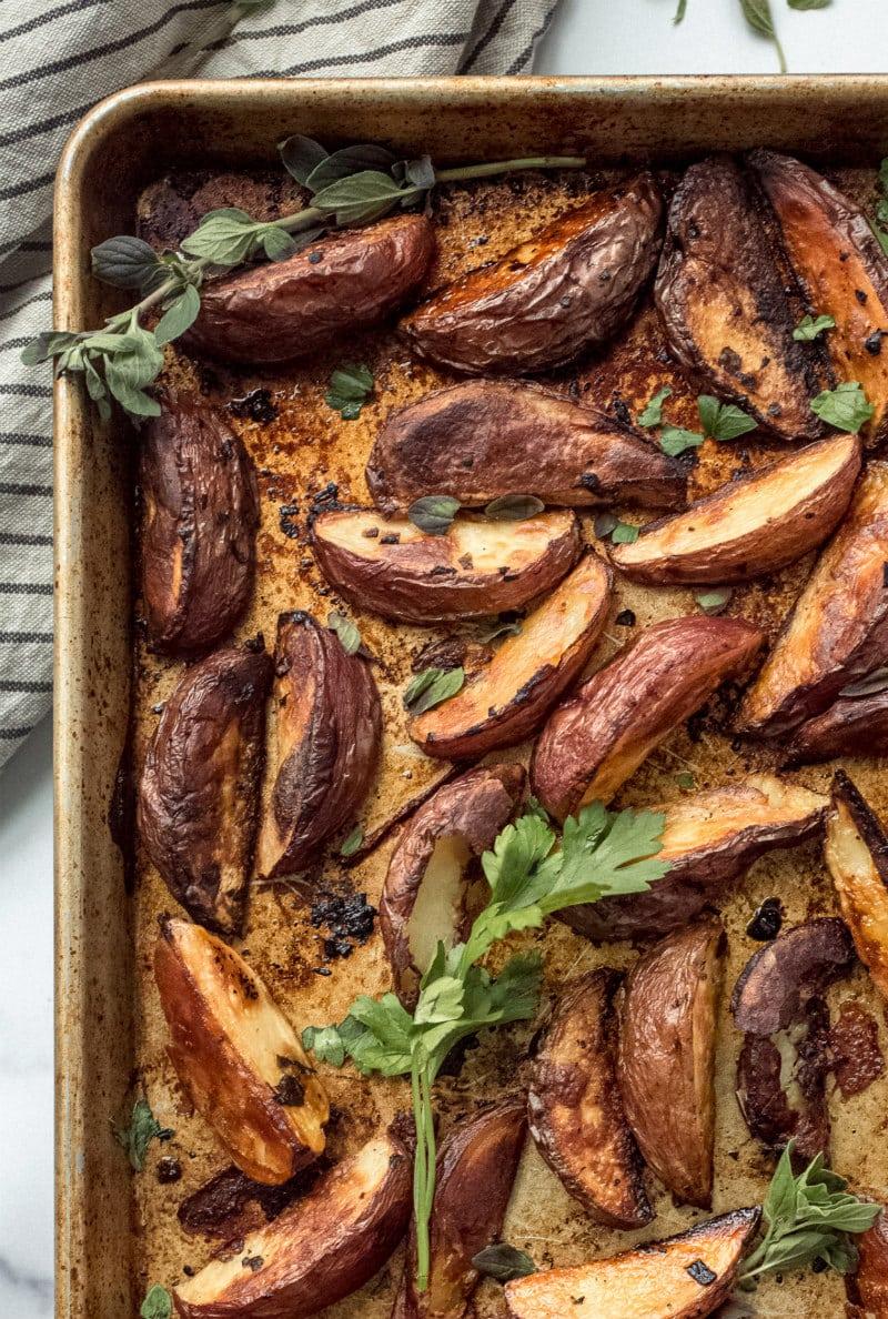 Greek Potato wedges on a baking sheet garnished with fresh oregano