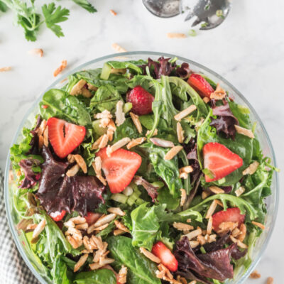 bowl of green salad with strawberries and sugared almonds