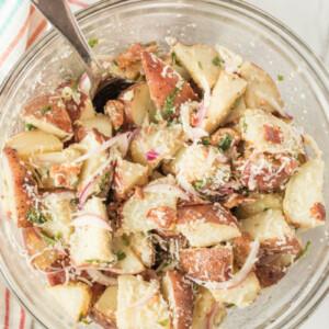 overhead shot of glass bowl with lemon basil roasted potato salad with a spoon set on a striped cloth napkin