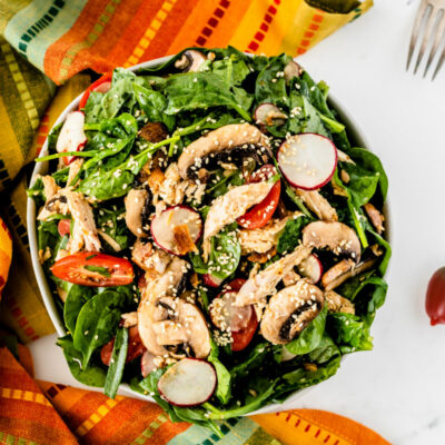 overhead shot of mandarin chicken spinach salad set on a bright striped cloth napkin