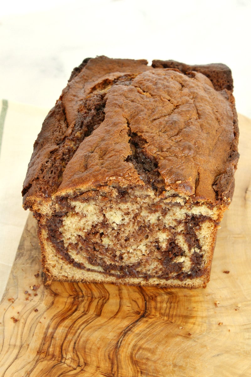 loaf of nutella banana bread on a cutting board, cut to see the inside of the bread
