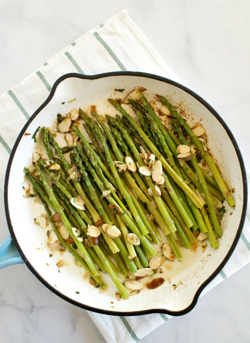 overhead shot of asparagus and almond butter in a white enamel skillet set on a white napkin with blue stripes