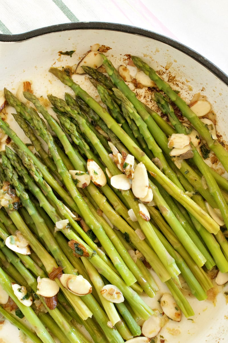 overhead shot of asparagus and almond butter being cooked in a white enamel skillet