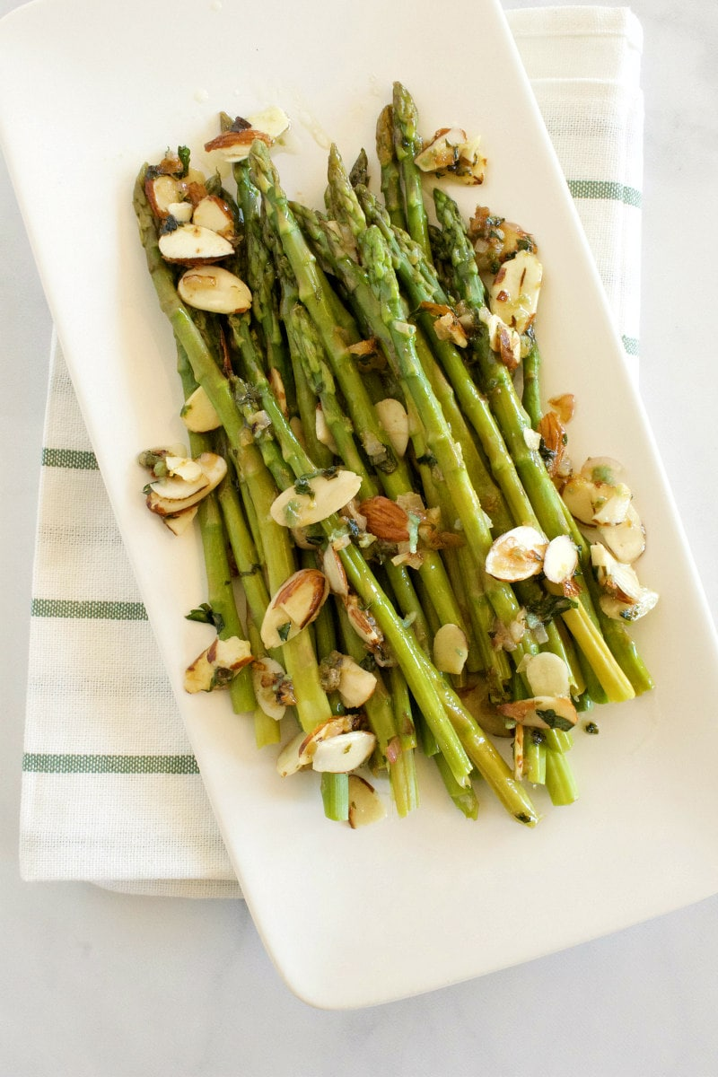 asparagus with almond butter displayed on a white platter and set on a white napkin with blue stripes