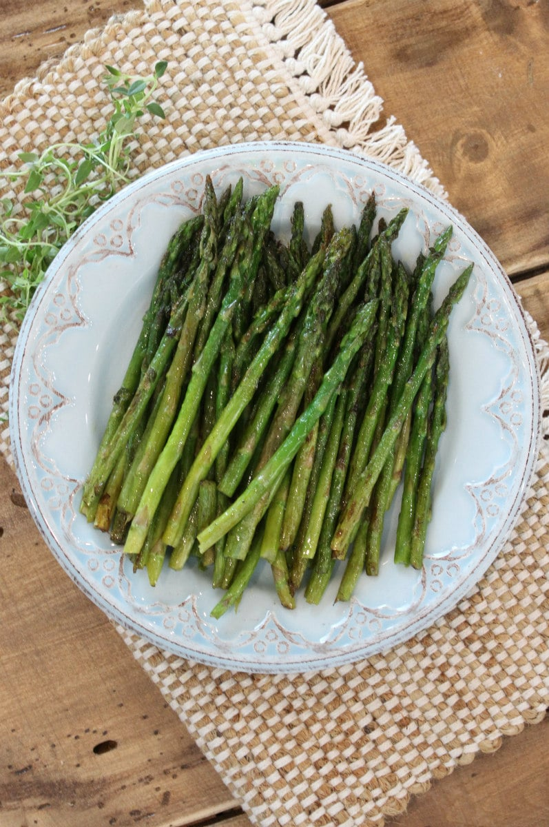 Pan Roasted Asparagus on a serving plate with fresh thyme