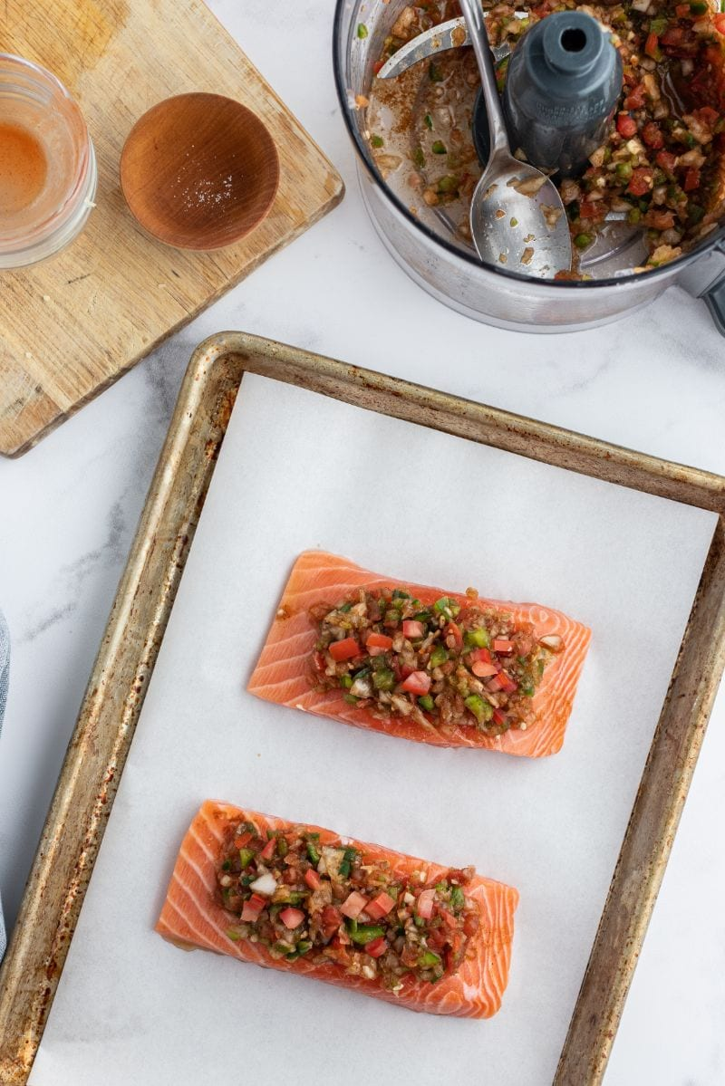 salsa topped salmon on baking sheet ready for oven