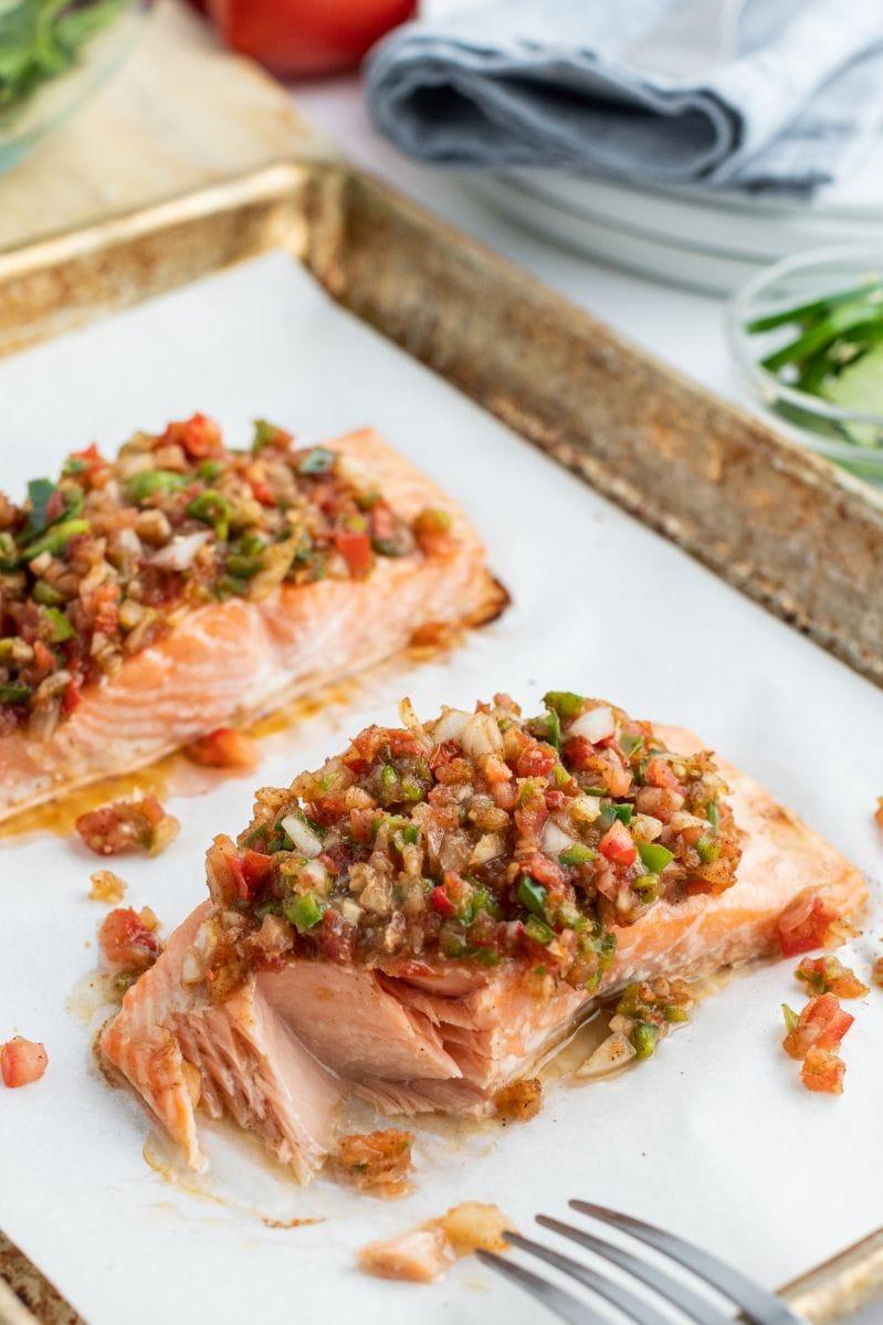 flaking away cooked salmon on baking sheet