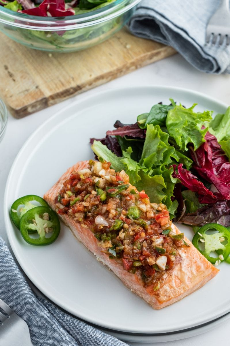 salsa roasted salmon on white plate with salad