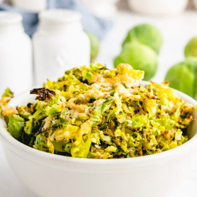 shredded parmesan brussels sprouts in white bowl