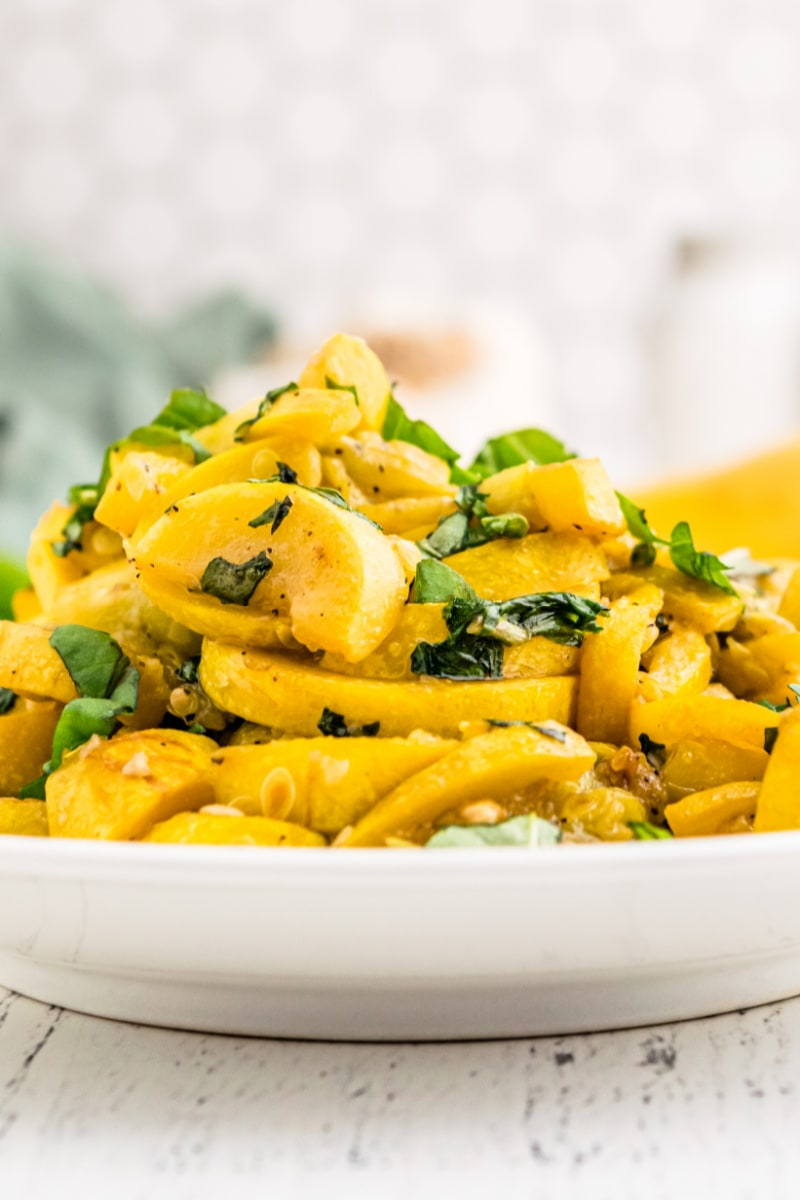 cooked squash and basil on a white plate
