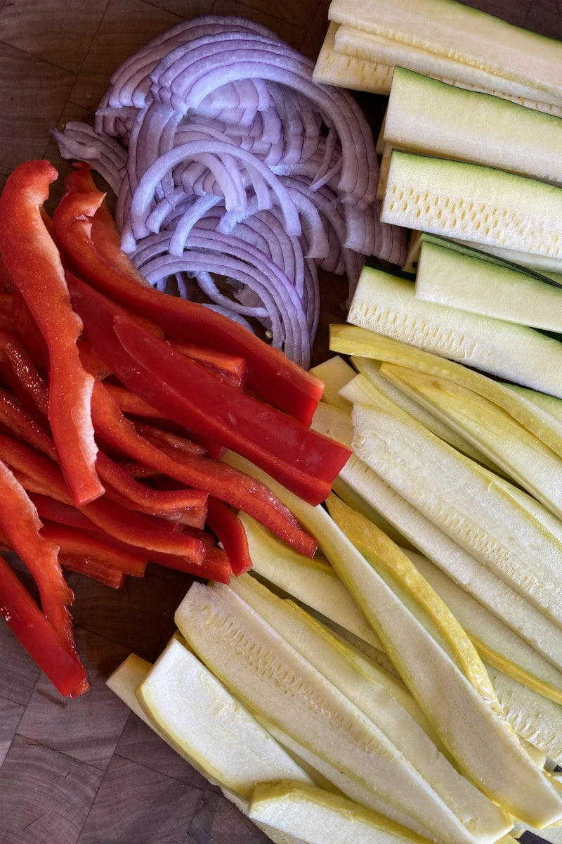 sliced vegetables displayed on a cutting board: red bell peppers, red onion, yellow squash and zucchini