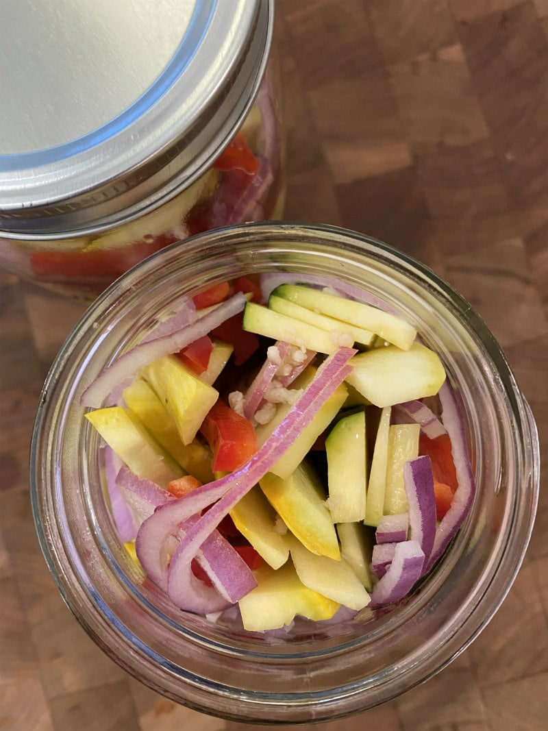 overhead shot looking into a jar that is marinating red onion, yellow squash, zucchini and red bell pepper