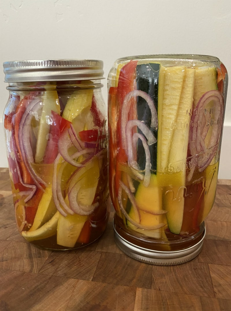 two jars marinating summer vegetables: yellow squash, red bell pepper, zucchini and red onion. one of the jars is turned upside down