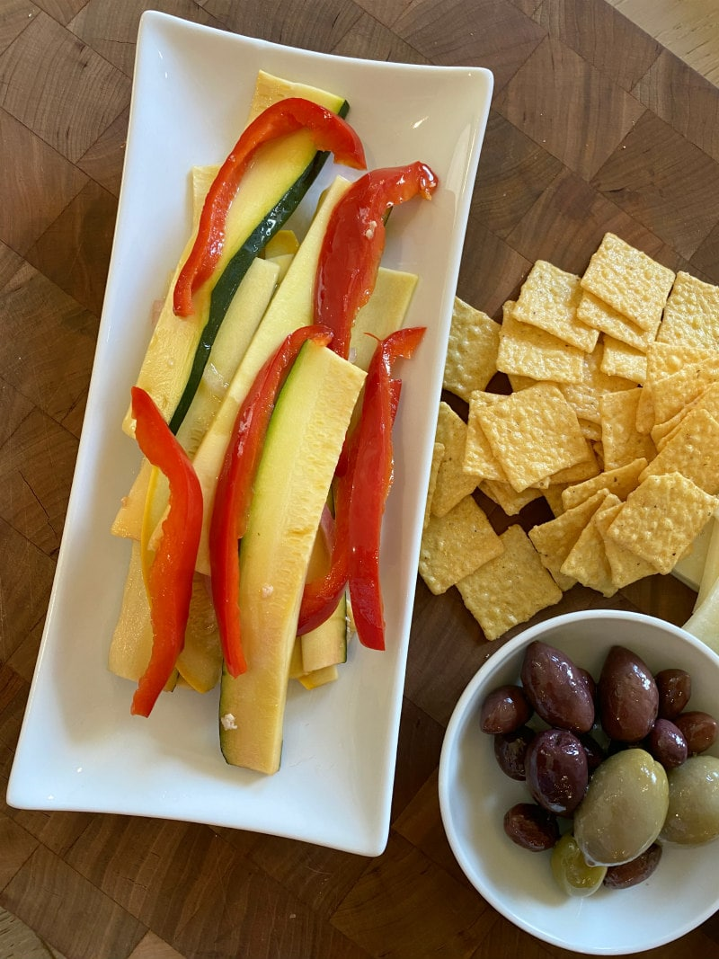 serving sweet and sour summer vegetables on a white plate displayed on a cutting board with crackers and a white bowl of olives
