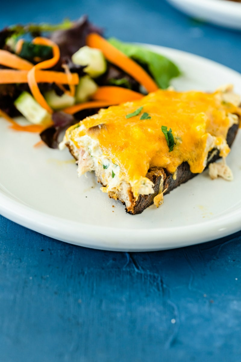 tuna melt on a white plate with salad
