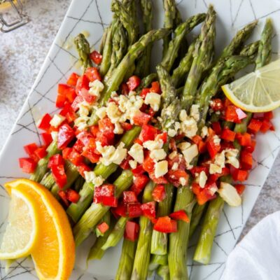 a white plate set on a marble background with chilled asparagus that are topped with feta vinaigrette with chopped red bell pepper and garnished with lemons and oranges
