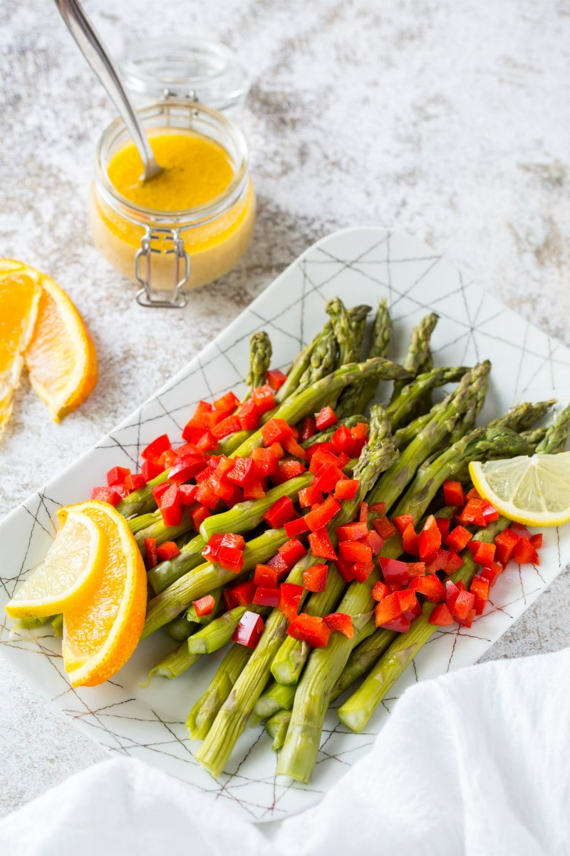 a white plate set on a marble background with chilled asparagus that are topped with feta vinaigrette with chopped red bell pepper and garnished with lemons and oranges. glass of vinaigrette on the side