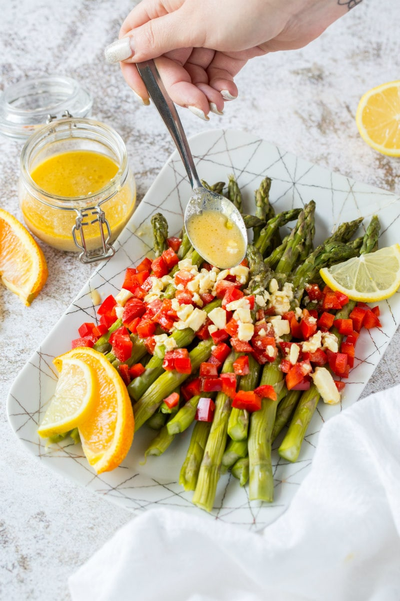 a white plate set on a marble background with chilled asparagus showing a hand spooning feta vinaigrette on top with chopped red bell pepper and garnished with lemons and oranges