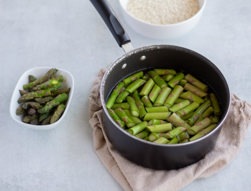 saucepan with water and asparagus pieces in it and a bowl of tips on the side