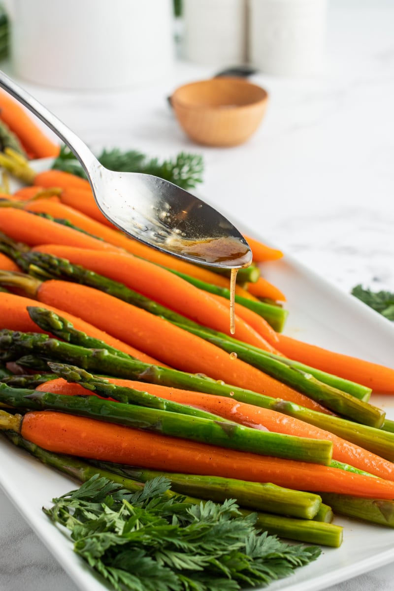 spooning maple butter sauce on carrots and asparagus