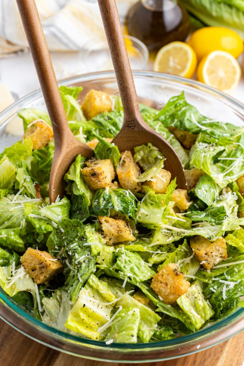 caesar salad with homemade sourdough croutons tongs tossing salad in bowl
